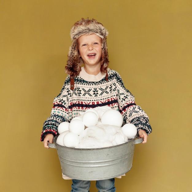 Вид спереди счастливого малыша в шапке и снежках Бесплатные Фотографии