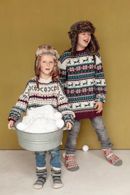 屋内で雪玉で遊ぶフルショット幸せな子供 無料写真