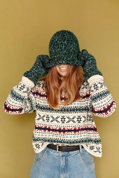 Средний снимок счастливая девушка закрыла лицо шляпой Бесплатные Фотографии