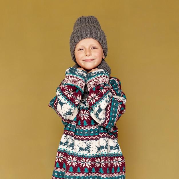 Средний снимок милый с теплой одеждой позирует Бесплатные Фотографии