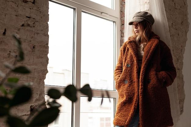 Низкий угол девушка с теплым пальто и шляпой Бесплатные Фотографии