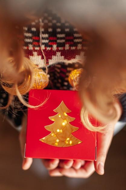 ギフトとクリスマスライトのクローズアップの女の子 無料写真