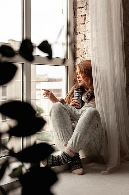 窓の外を見てフルショットの女の子 無料写真