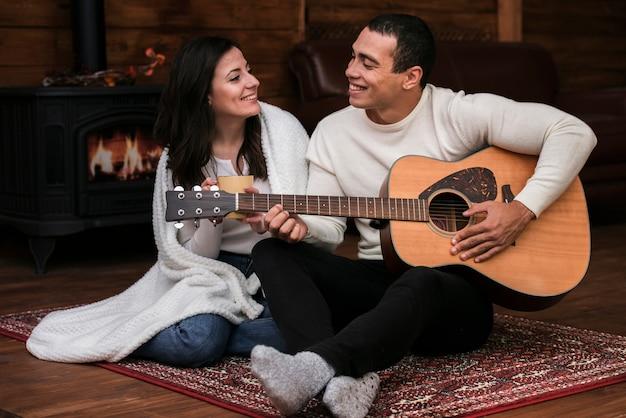 Молодой человек играет на гитаре женщине Бесплатные Фотографии