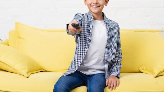 Улыбающийся ребенок держит пульт дистанционного управления Бесплатные Фотографии