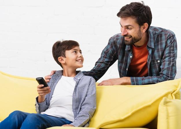 リモコンを押しながら父親を見ている息子 無料写真