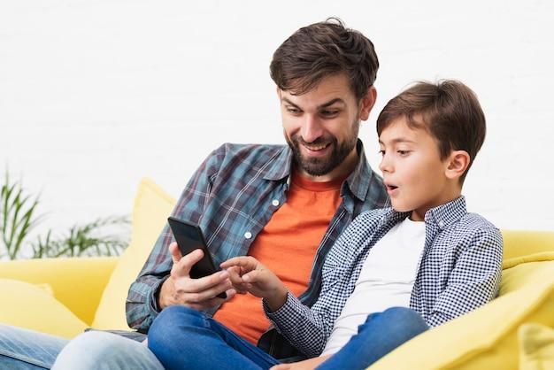 電話で見ている驚いた息子と父親 無料写真