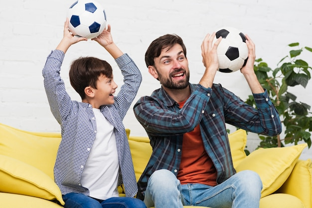 父と息子のサッカーボールを保持 無料写真