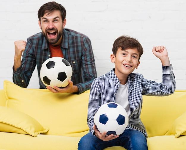 興奮して父と息子のサッカーの試合を見て 無料写真