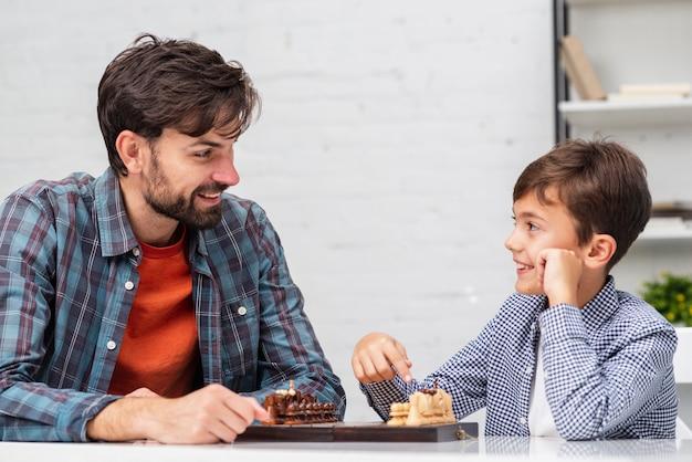 Отец и сын играют в шахматы и смотрят друг на друга Бесплатные Фотографии