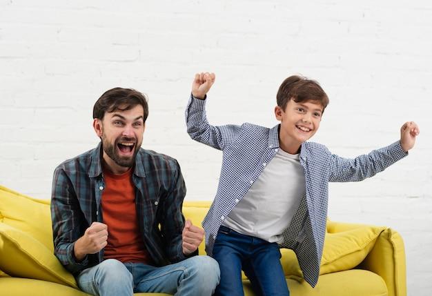 Возбужденный сын и отец сидят на диване Бесплатные Фотографии