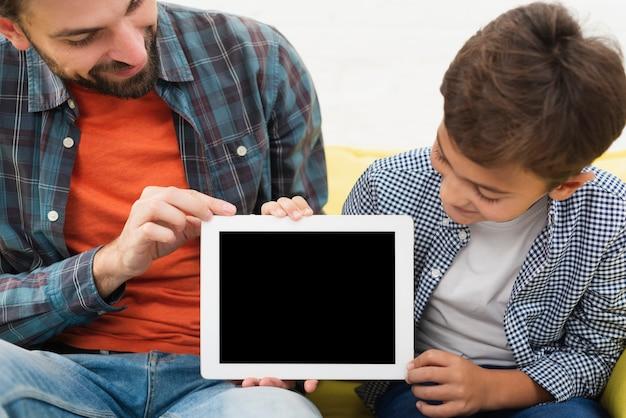 Отец и сын держат макет фото Бесплатные Фотографии