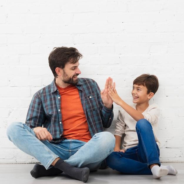 Отец и сын сидят на полу и высокие пять Бесплатные Фотографии