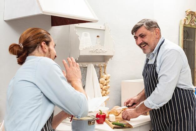 笑顔の父と息子の料理とお互いを見て 無料写真