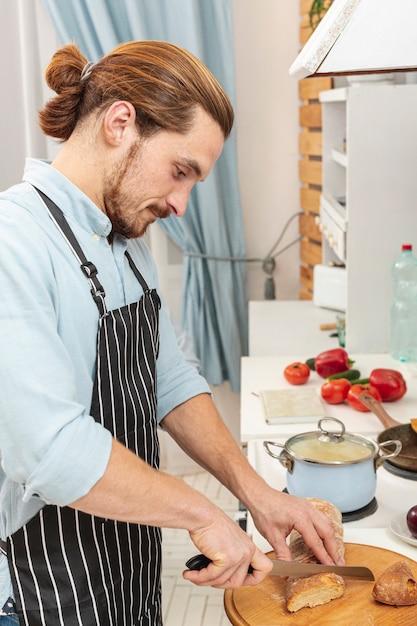 ハンサムな若い男がパンを切る 無料写真