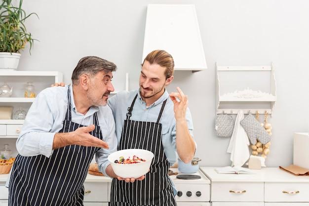 サラダについて話している父と息子 無料写真
