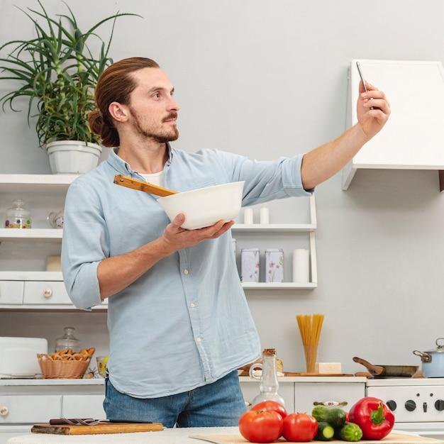 Человек, принимая селфи с кухонной миской Бесплатные Фотографии