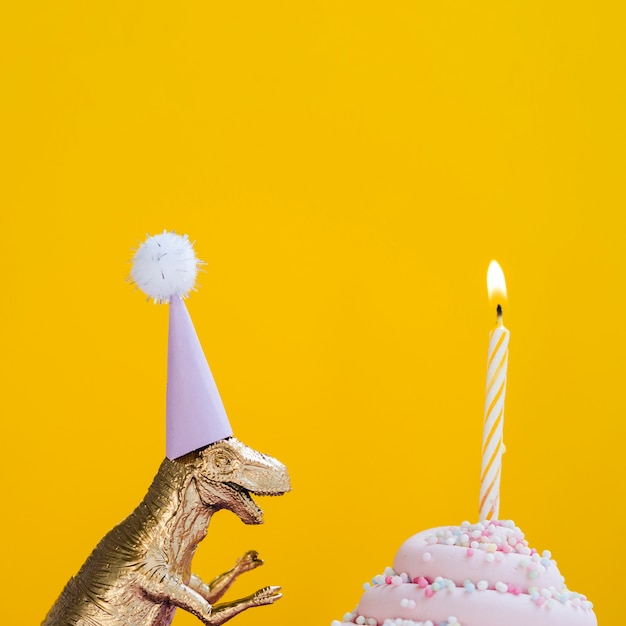 誕生日の帽子とおいしいマフィンを持つ恐竜 無料写真
