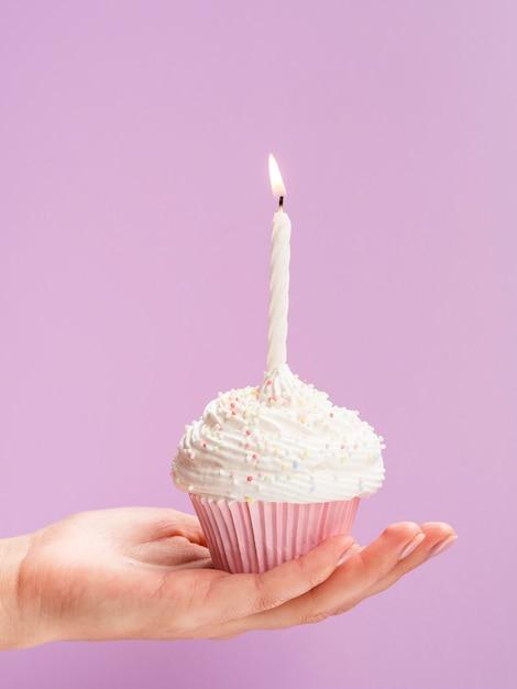 誕生日のマフィンを持っているクローズアップ手 無料写真