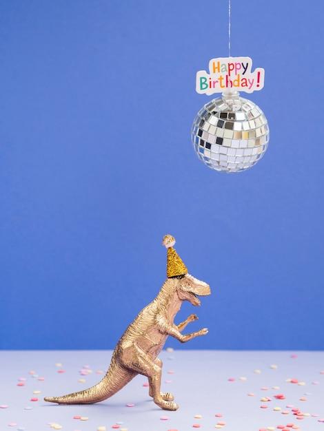 誕生日の帽子とディスコグローブとおもちゃの恐竜 無料写真