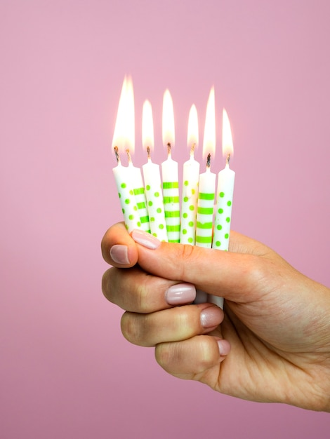 ピンクの背景に誕生日の蝋燭を持っている手 無料写真