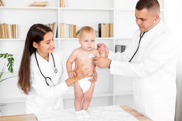 聴診器で愛らしい小さな赤ちゃんを聞いて医師 無料写真