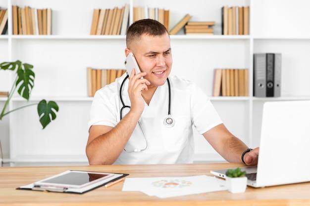 電話で話している若い男性医師 無料写真