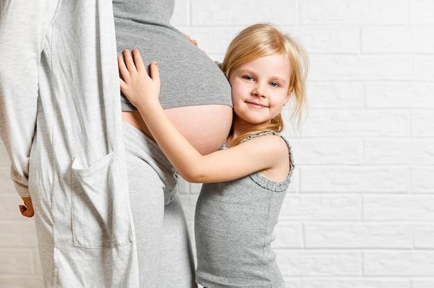 母の妊娠中の腹を抱きしめるかわいい女の子 無料写真