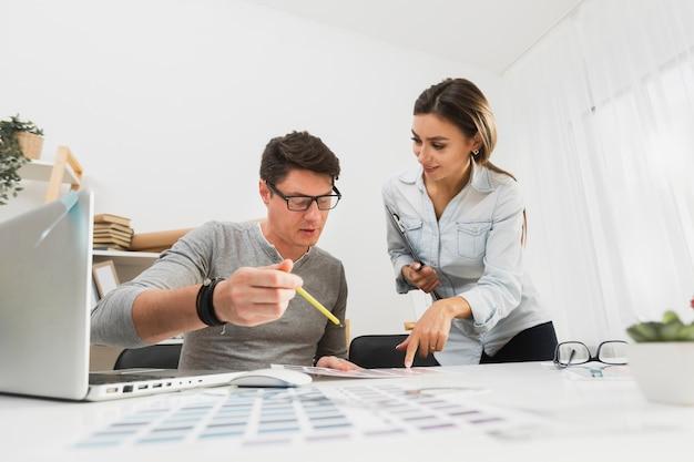 Вид спереди мужчина и женщина, работающая на деловых бумагах Бесплатные Фотографии