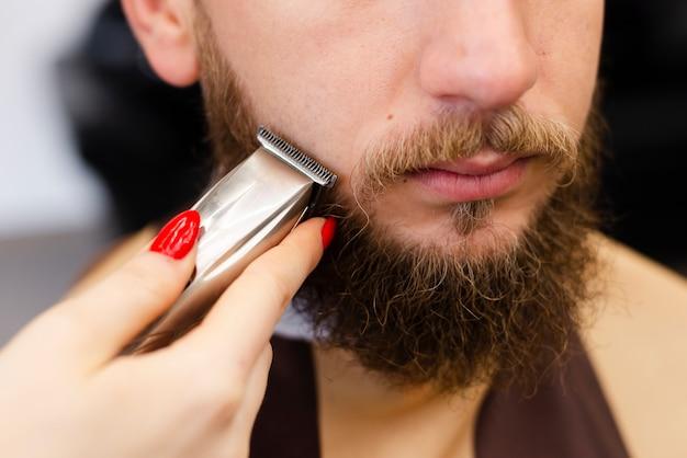彼女のクライアントのひげのクローズアップを剃る女性 無料写真