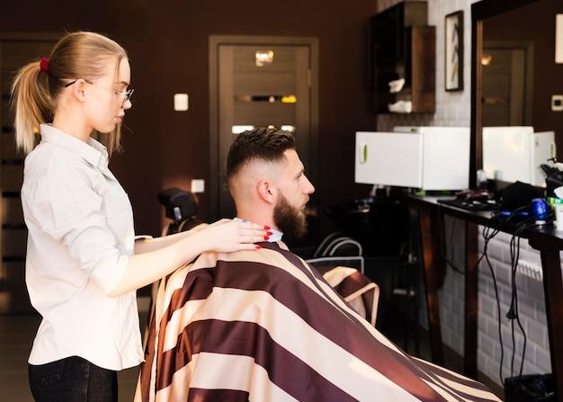 彼女のクライアントに散髪を与える準備をしてサイドビュー女性 無料写真