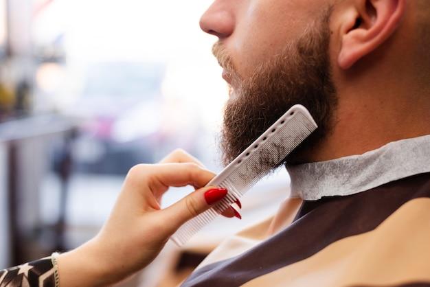 Женщина ухаживает за мужской бородой в парикмахерской Бесплатные Фотографии