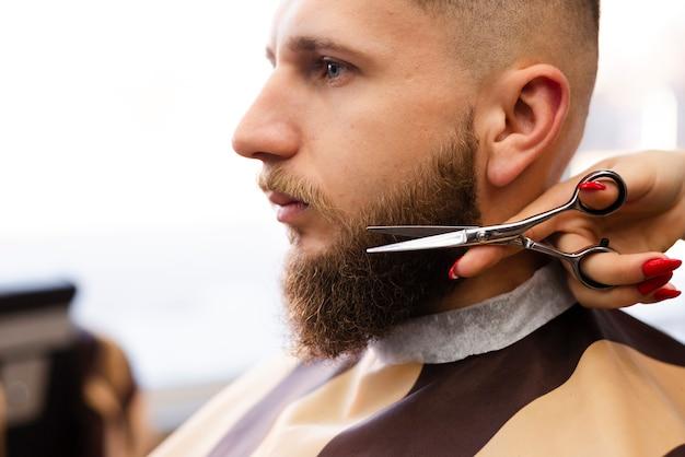 プロの理髪店で男のひげを切る女性 無料写真