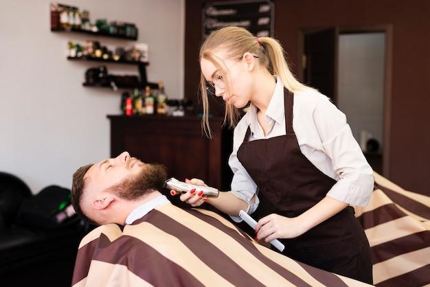 Женщина бреет усы своего клиента в парикмахерской Бесплатные Фотографии