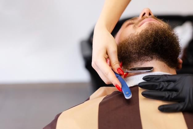 Женщина бреет бороду клиента с копией пространства Бесплатные Фотографии