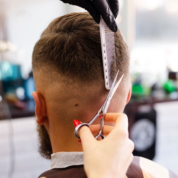 Вид сзади женщина обрезает волосы своего клиента крупным планом Бесплатные Фотографии