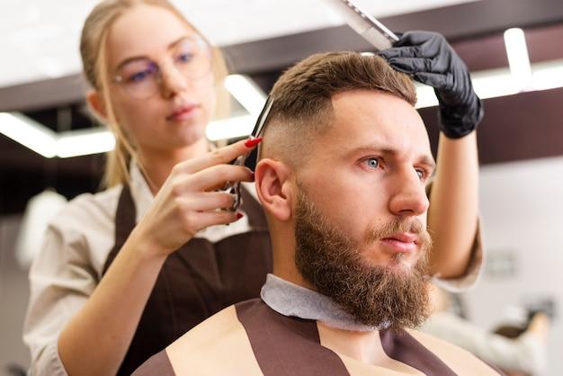 Низкая женщина, подстригающая волосы клиента Бесплатные Фотографии