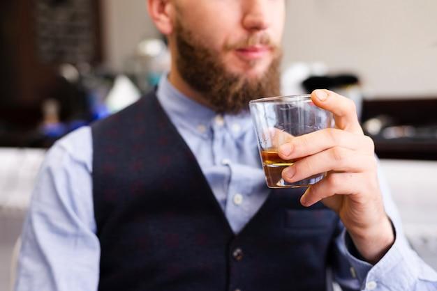 理髪店で彼の飲み物を持って男 無料写真