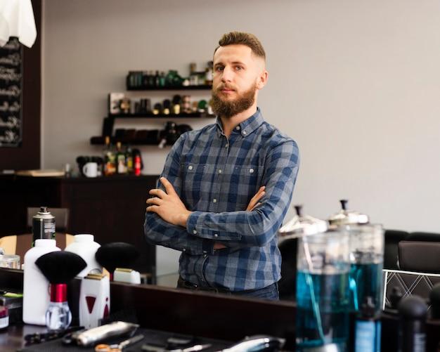 理髪店の鏡で自分を見ている男 無料写真