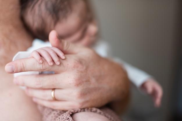 彼の赤ちゃんの手を握ってクローズアップのお父さん 無料写真