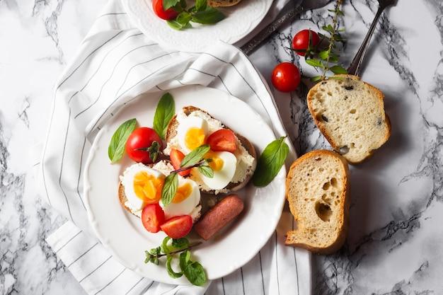 チーズのゆで卵トマトとホットドッグのトップビューパン 無料写真