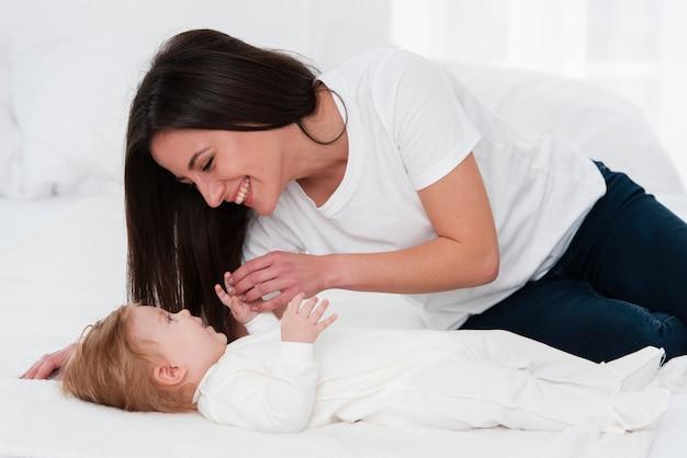 ベッドで赤ちゃんと遊ぶ女性 無料写真
