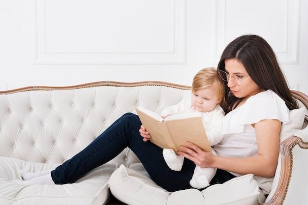 母は赤ちゃんとソファで読書 無料写真