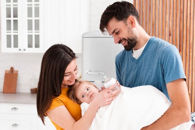 毛布で赤ちゃんを保持している親 無料写真