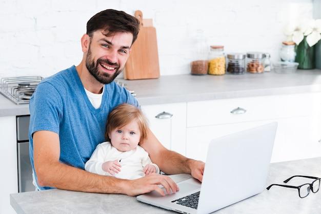 赤ちゃんとラップトップに取り組んでいる間笑顔のお父さん 無料写真