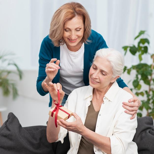 Зрелая женщина дарит подруге подарок Бесплатные Фотографии