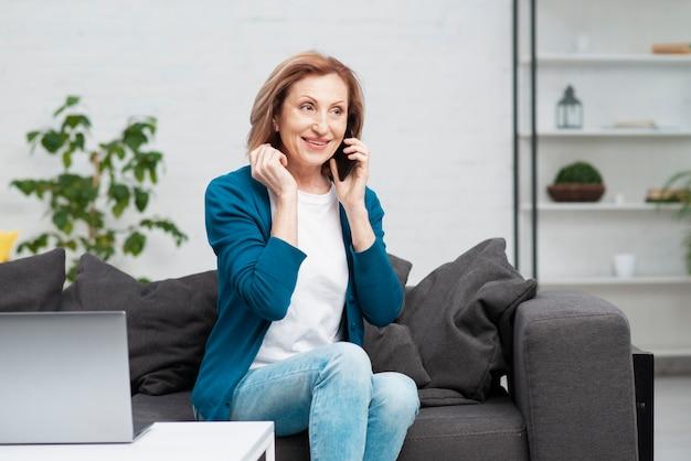 電話で話している年配の女性の肖像画 無料写真