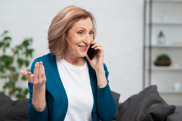 電話で話しているかわいい年配の女性 無料写真