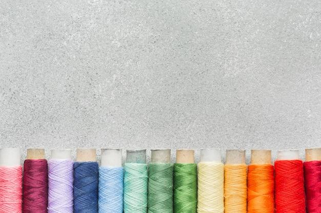 コピースペースで虹色とりどりのミシン糸 無料写真