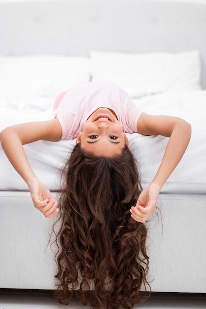 頭ぶら下げとベッドの端に正面少女 無料写真